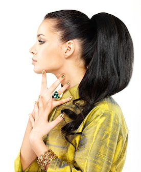 Hübsche frau mit goldenen nägeln und schönem edelstein-smaragd
