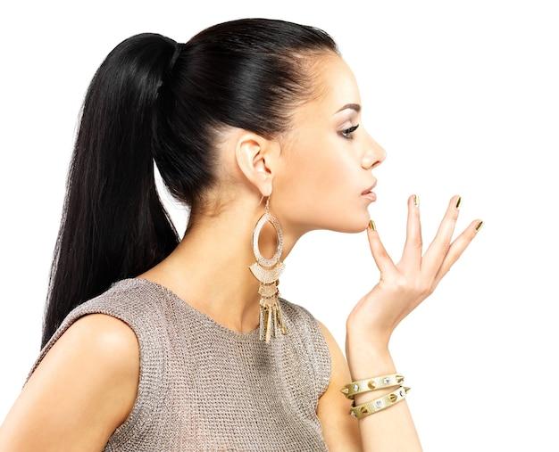 Hübsche frau mit goldenen nägeln und schönem goldschmuck lokalisiert auf weiß