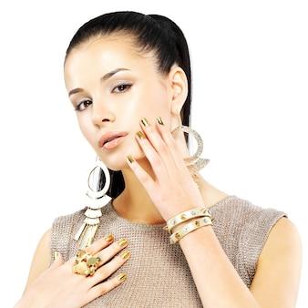 Hübsche frau mit goldenen nägeln und schönem goldschmuck lokalisiert auf weißem hintergrund