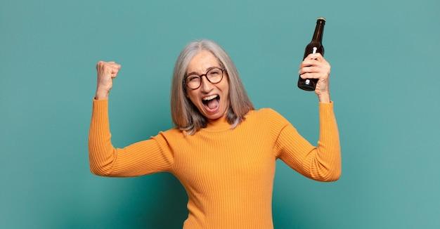 Hübsche frau mit grauem haar, die ein bier trinkt