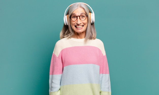 Hübsche frau mit grauen haaren, die mit ihren kopfhörern musik hört