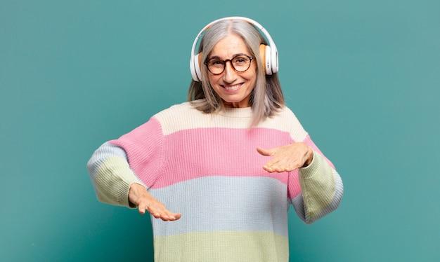 Hübsche frau mit grauen haaren, die musik mit ihren kopfhörern hört