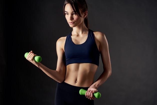 Hübsche frau mit hanteln in der hand mit trainingsübungen im fitnessstudio