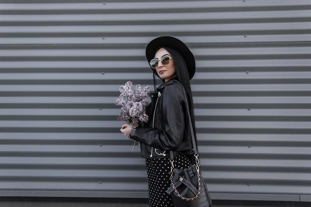 Hübsche frau mit hut in trendiger sonnenbrille in schwarzer modischer frühlingskleidung mit ledertasche mit lila blumen in den händen ruht am frühlingstag in der nähe der metallwand im freien. sexy mädchen im mode-outfit.