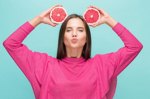 Hübsche frau mit köstlicher grapefruit im arm