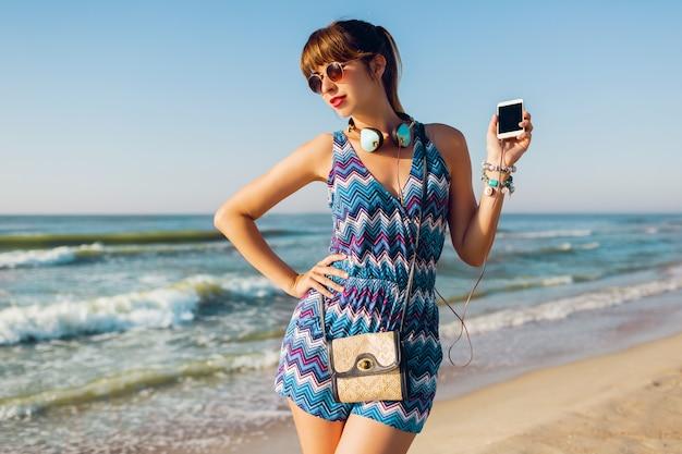 Hübsche frau mit kopfhörern am strand
