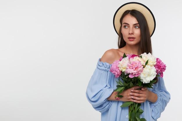 Hübsche frau mit langen brünetten haaren. trägt einen hut und ein blaues hübsches kleid. hält einen strauß schöner blumen