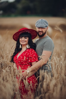 Hübsche frau mit langen dunklen welligen haaren im roten kleid umarmt mit ihrem schönen freund im grauen t-shirt