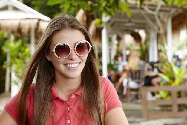 Hübsche frau mit langen glatten haaren, die mit freudigem lächeln schauen, glücklich mit frischer luft und heißem sonnigem wetter während ihrer ferien im exotischen land