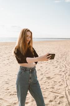 Hübsche frau mit langen haaren, blondine macht foto auf handy am sandstrand im sommer