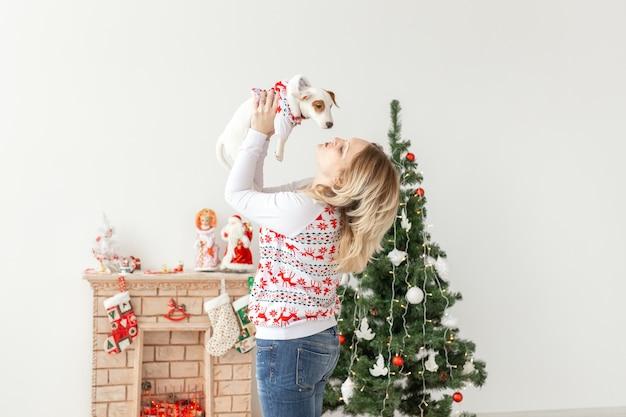 Hübsche frau mit lustigem welpen jack russell terrier über weihnachtsbaumhintergrund
