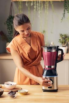 Hübsche frau mit mixer, die fruchtsmoothie zubereitet