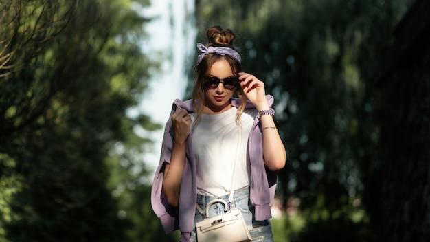 Hübsche frau mit modischem bandana und stilvoller sonnenbrille in sportlicher freizeitkleidung geht im park spazieren