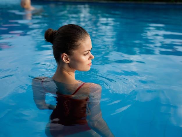 Hübsche frau mit nackten schultern in einem badeanzug steht in der rückansicht des pools
