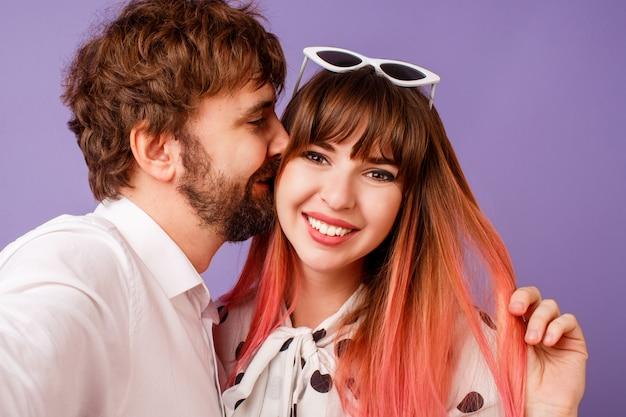 Hübsche frau mit offenem lächeln und rosa haaren, die mit ihrem freund mit bart aufwerfen