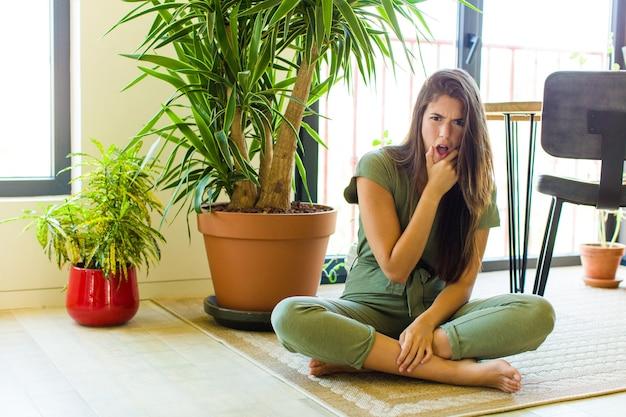 Hübsche frau mit offenem mund und weit geöffneten augen und hand am kinn, die sich unangenehm geschockt fühlt und sagt, was oder wow