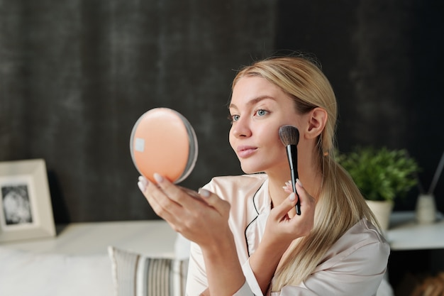 Hübsche frau mit pinsel, die puder auf ihr gesicht aufträgt und im spiegel schaut, während natürliches make-up tut