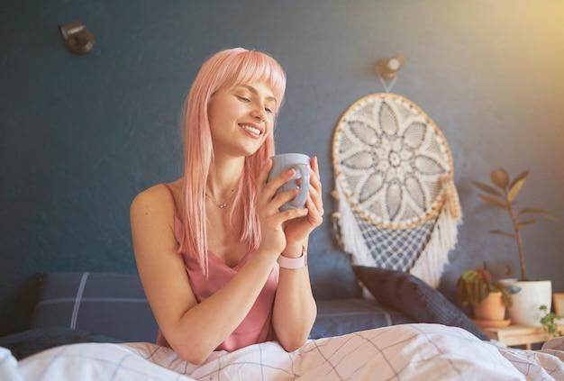 Hübsche frau mit rosa haaren hält eine tasse auf einem bequemen bett mit einer weichen decke