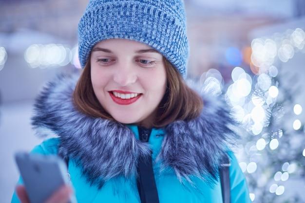 Hübsche frau mit rot lackierten lippen, hat ein angenehmes lächeln, verbringt freizeit im freien, genießt den winterabend in der stadt, benutzt ein smartphone