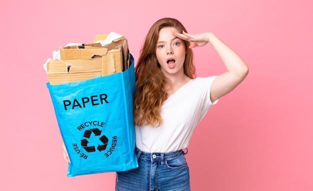 Hübsche frau mit rotem kopf, die glücklich, erstaunt und überrascht aussieht und eine recyclingpapiertüte hält