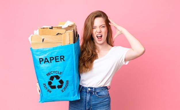 Hübsche frau mit rotem kopf, die mit den händen in die luft schreit und eine recyclingpapiertüte hält