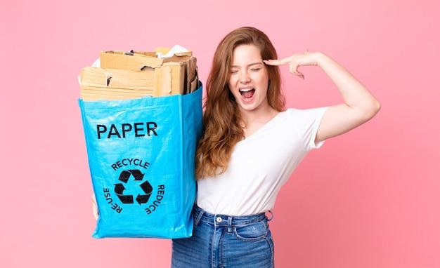 Hübsche frau mit rotem kopf, die unglücklich und gestresst aussieht, selbstmordgeste, die ein waffenzeichen macht und eine recyclingpapiertüte hält