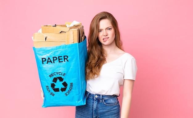 Hübsche frau mit rotem kopf, die verwirrt und verwirrt aussieht und eine recyclingpapiertüte hält?