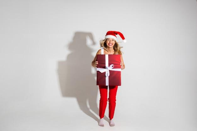 Hübsche frau mit rotem und weißem weihnachtshut hält eine große schachtel mit geschenk und freut sich