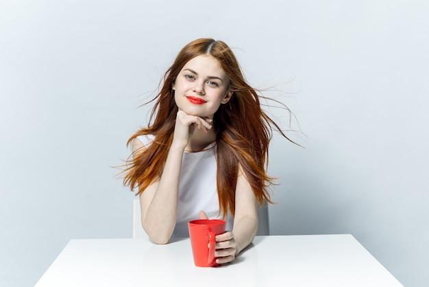Hübsche frau mit roten lippen, die am tisch eine tasse mit einem getränk sitzen, das in einem café entspannt
