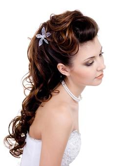 Hübsche frau mit schöner hochzeitsfrisur, lange lockige haare lokalisiert auf weiß