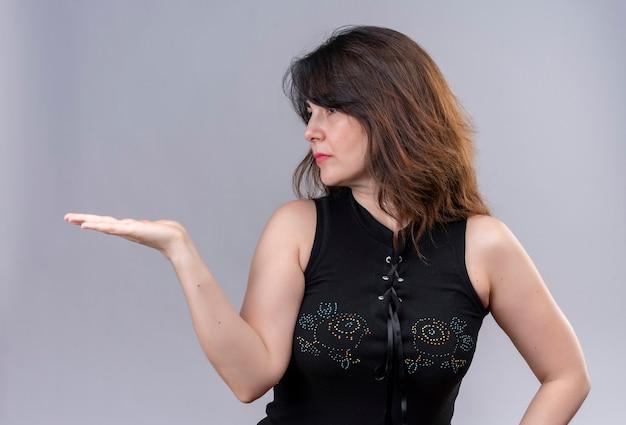 Hübsche frau mit schwarzer bluse, die nach rechts schaut und etwas an ihrer rechten hand hält