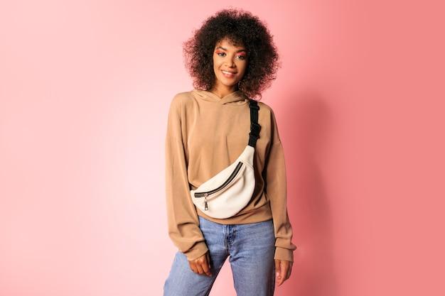 Hübsche frau mit schwarzer haut und stilvoller afrikanischer frisur im sportlichen outfit, das auf rosa aufwirft