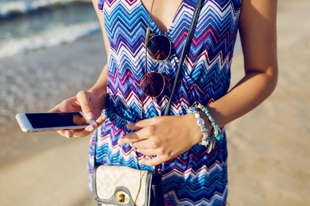 Hübsche frau mit smartphone am strand
