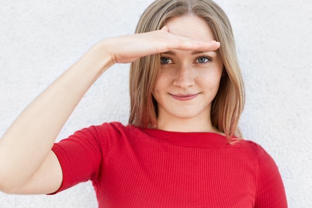 Hübsche frau mit sommersprossen und hellem haar, die roten pullover trägt, der ihre hand auf stirn hält