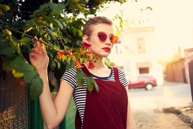 Hübsche frau mit sonnenbrille im freien mode posiert blumen. foto in hoher qualität