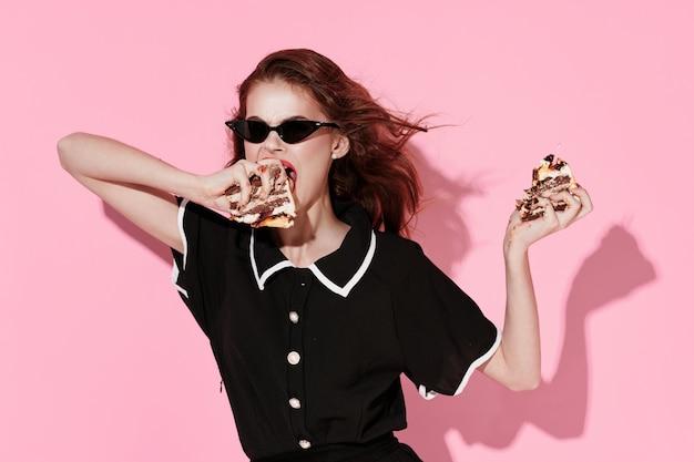 Hübsche frau mit sonnenbrille mit kuchen in den händen von süßigkeiten