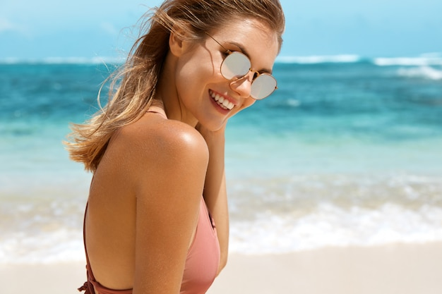 Hübsche frau mit sonnenbrille und badeanzug am strand