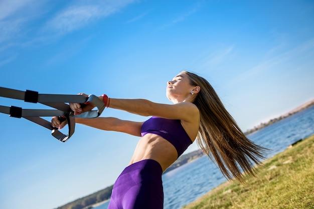 Hübsche frau mit sportbekleidung, die tagsüber crossfit-liegestütze mit trx-fitnessgurten im freien nahe dem see tut. gesunder lebensstil