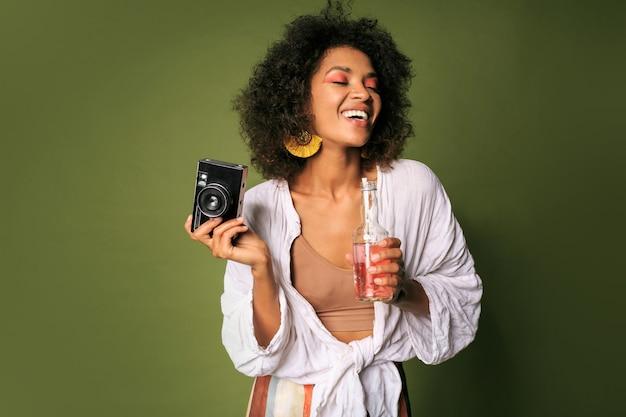 Hübsche frau mit stislischer frisur, die mit kamera aufwirft und limonade trinkt