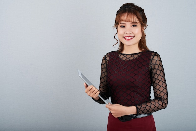 Hübsche frau mit tablet-computer lächelnd an der kamera gegen grau
