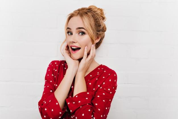 Hübsche frau mit überraschtem lächeln, das ihr gesicht auf weißer wand berührt. europäisches blondes mädchen, das im roten pyjama aufwirft.