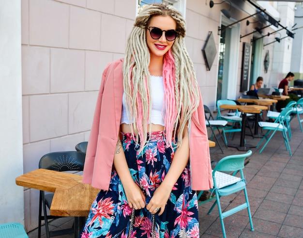 Hübsche frau mit ungewöhnlicher dreads-frisur, die auf der straße aufwirft und rosa blumen femininen eleganten blick trägt