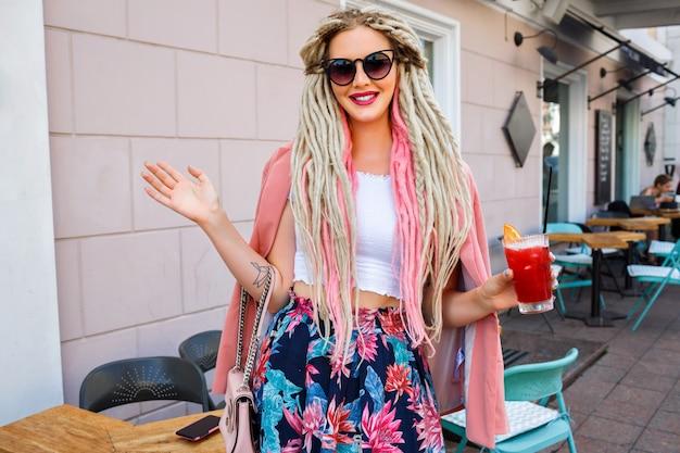 Hübsche frau mit ungewöhnlicher dreads-frisur, die auf der straße posiert, rosa blumen femininen eleganten blick trägt und frische limonade hält