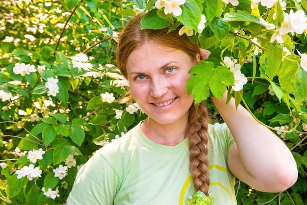 Hübsche frau mit weißen jasminblüten im sonnigen park
