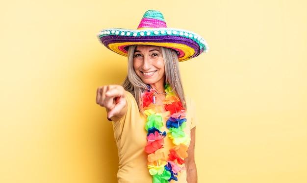 Hübsche frau mittleren alters, die auf die kamera zeigt, die sie wählt. mexikanisches partykonzept