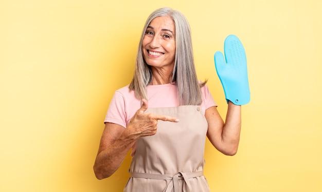 Hübsche frau mittleren alters, die aufgeregt und überrascht aussieht und auf die seite zeigt. ofenhandschuh-konzept