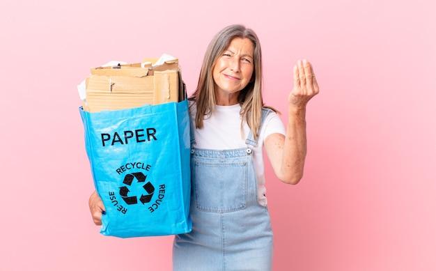 Hübsche frau mittleren alters, die capice oder geldgeste macht und ihnen sagt, dass sie das recycling-kartonkonzept bezahlen sollen