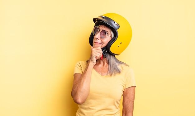 Hübsche frau mittleren alters, die denkt, sich zweifelhaft und verwirrt fühlt. motorradhelmkonzept