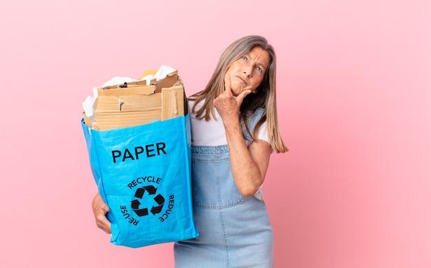 Hübsche frau mittleren alters, die denkt, sich zweifelhaft und verwirrt fühlt, recycling-kartonkonzept