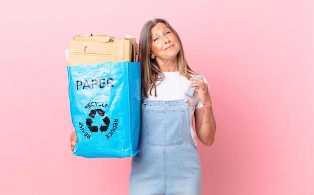 Hübsche frau mittleren alters, die ein arrogantes, erfolgreiches, positives und stolzes recycling-kartonkonzept sieht